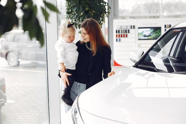 Elegante vrouw met dochtertje in een auto salon