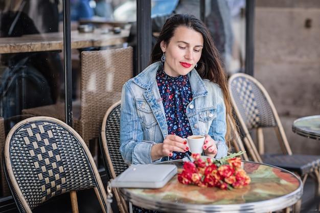 Elegante vrouw met lang donkerbruin haar in een blauwe jurk zit alleen met bloemen in het straatcafé en koffie drinken
