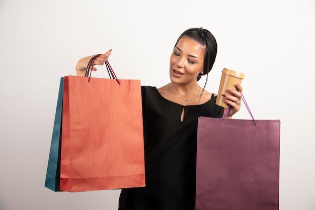Elegante vrouw met stelletje boodschappentassen en kopje koffie.