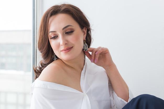 Elegante vrouw met zilveren juwelenoorringen en ketting