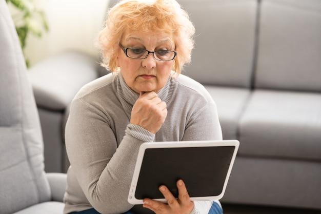 Elegante vrouw van middelbare leeftijd met behulp van digitale tablet thuis.