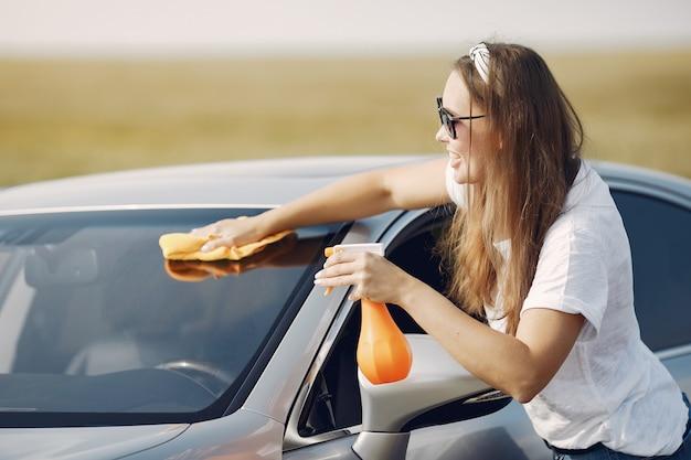 Elegante vrouw veegt de auto af met een doek