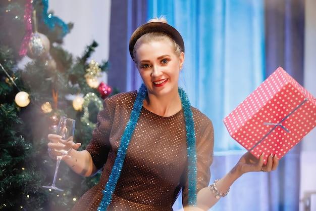 Elegante vrouw verheugt zich met een geschenkdoos in de buurt van een kerstboom. een vrouw lacht, glimlacht, poseert. speciale vintage ruis- en graanfilter, wazige lichten.