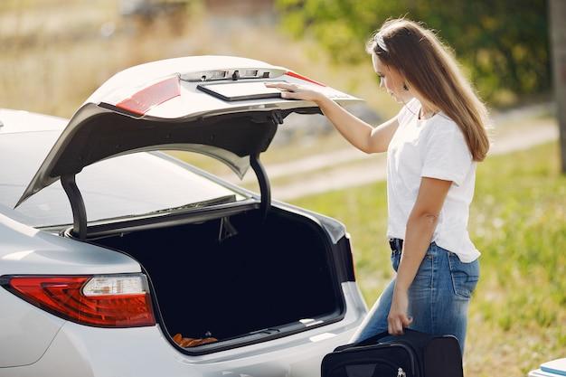 Elegante vrouw verwijdert de koffer uit de kofferbak