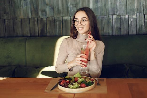 Elegante vrouw zitten aan de tafel met cocktail en salade