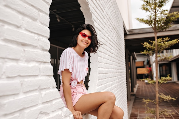 Elegante vrouw zittend op de muur en camera kijken. buiten schot van charmante jonge vrouw poseren met oprechte glimlach op straat.