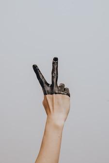 Elegante vrouwelijke hand gedoopt in zwarte verf. geïsoleerd. gebaar.