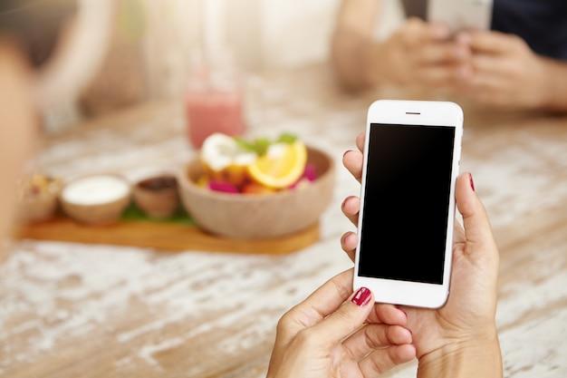 Elegante vrouwelijke handen met nette rode nagels met behulp van witte mobiele telefoon, nieuwsfeed bekijken via haar account op sociale netwerken