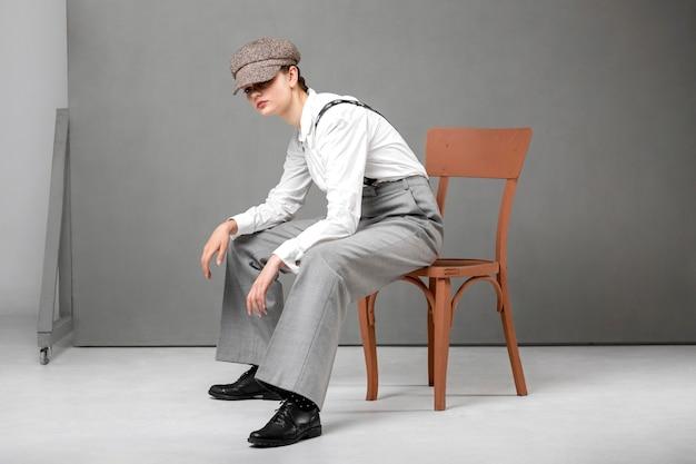 Elegante vrouwelijke model poseren in een stoel in een elegant wit overhemd en bretels. nieuw vrouwelijkheidsconcept