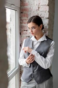 Elegante vrouwelijke model poseren in een venster in een elegante gilet. nieuw vrouwelijkheidsconcept