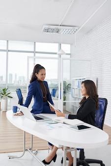 Elegante vrouwelijke ondernemers bespreken rapport met jaarstatistieken voordat ze de ceo van het bedrijf ontmoeten