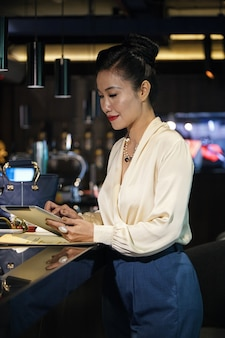 Elegante vrouwelijke restauranteigenaar die aan de toog staat en op tabletcomputer werkt