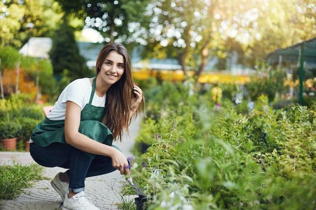 Elegante vrouwelijke tuinman-assistent die voor planten in een buitengroenwinkel zorgt.