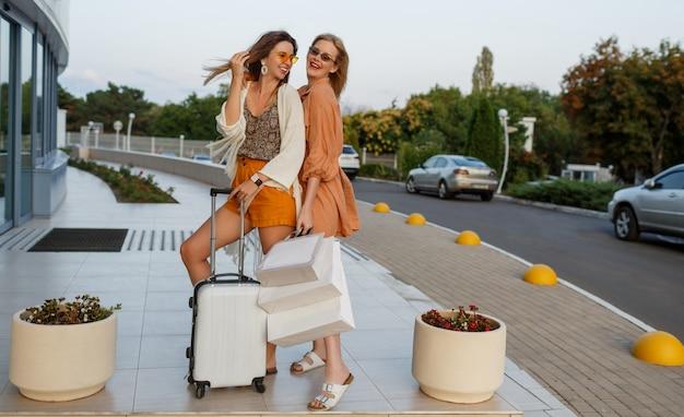 Elegante vrouwen na het verlaten van reis en winkelen die openlucht dichtbij luchthaven stellen