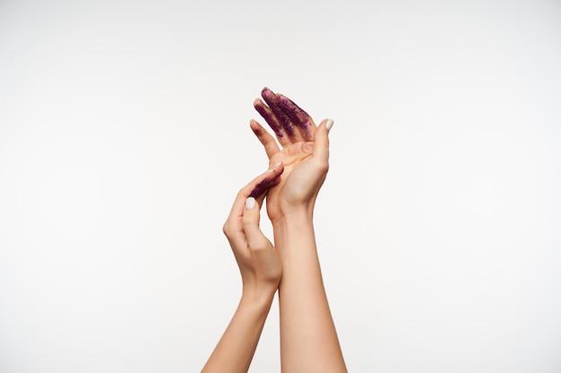Elegante vrouwtjes, mooie handen die elkaar zachtjes aanraken en worden geverfd met violette glitters, poseren op wit. menselijke lichaamstaal concept
