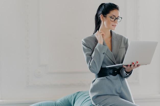 Elegante welvarende vrouw concentreerde zich op online communicatie