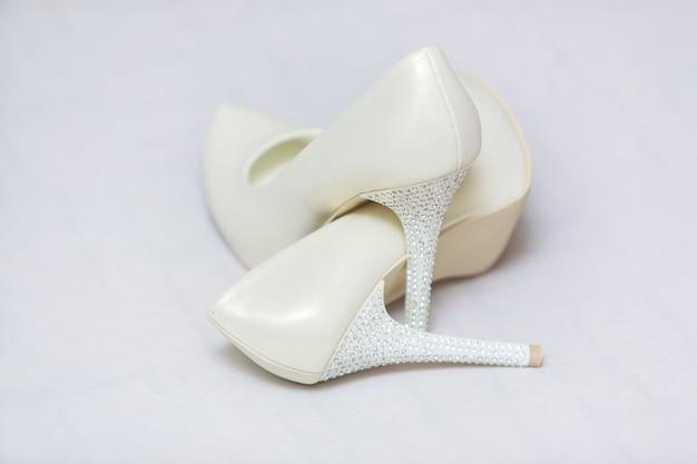 Elegante witte bruidsschoenen met hoge hakken op wit versierd met strass steentjes.