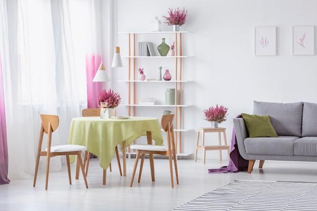 Elegante woonkamer met houten stoelen ronde tafel met olijfgroen tafelkleed grijze bank