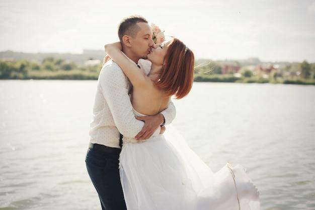Elegante zachte stijlvolle bruidegom en bruid in de buurt van rivier of meer. bruidspaar verliefd