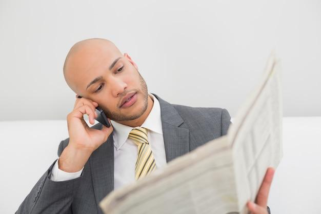 Elegante zakenman die cellphone gebruiken terwijl het lezen van krant