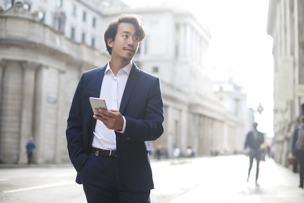 Elegante zakenman die in de straat loopt, die een blauw kostuum draagt