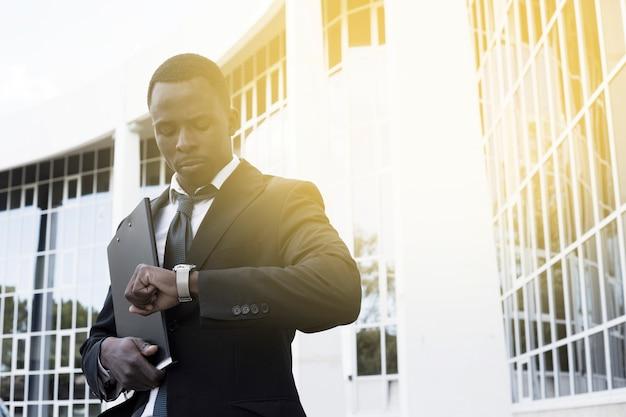 Elegante zakenman die tijd controleert