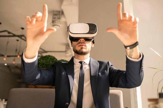 Elegante zakenman in formalwear en vr-headset zitten in café terwijl virtueel display wordt aangeraakt tijdens de presentatie