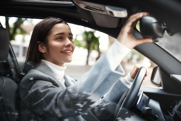 Elegante zakenvrouw achteruitkijkspiegel kijken, aanpassen voor rijden