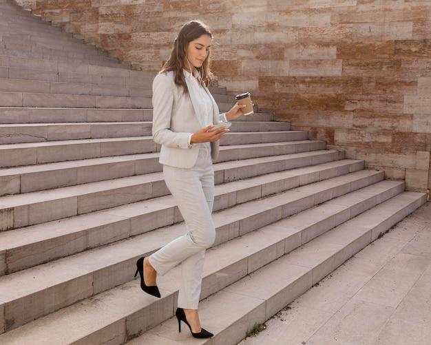 Elegante zakenvrouw op trappen buiten met smartphone en koffie