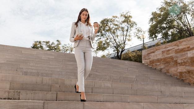 Elegante zakenvrouw op trappen buitenshuis