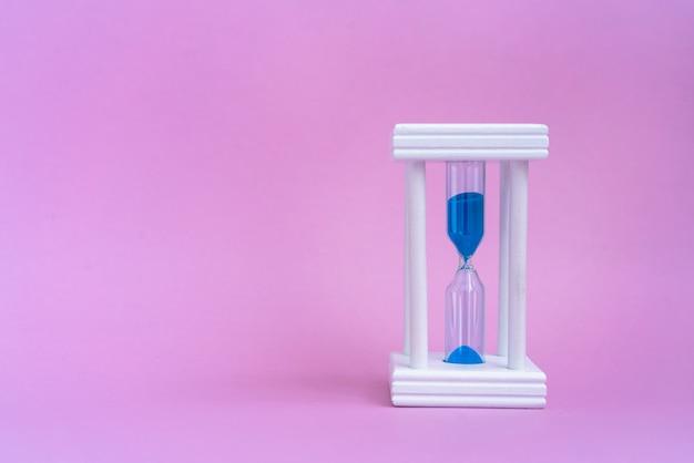 Elegante zandloper met blauw zand op roze achtergrond met kopie