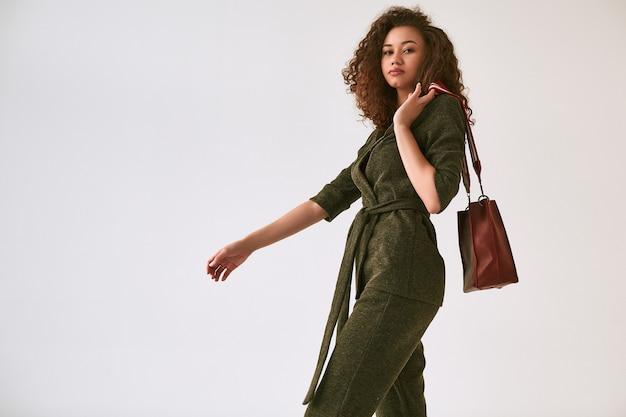 Elegante zwarte vrouw met krullend haar in trendy groen pak