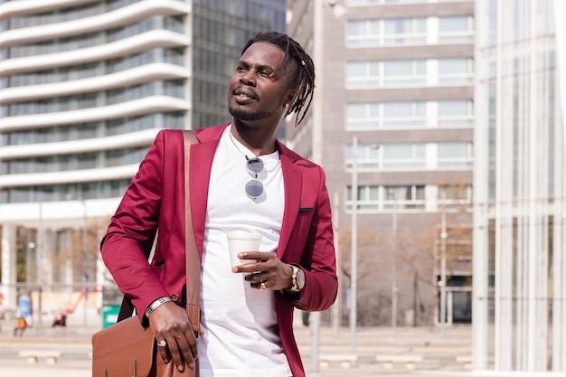 Elegante zwarte zakenman loopt door het financiële centrum van de stad met een kopje koffie en een aktetas, kopieer ruimte voor tekst