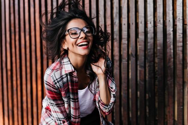 Elegante zwartharige meisje dansen op houten muur. charmante latijns-vrouw in glazen postivie emoties uitdrukken en lachen.