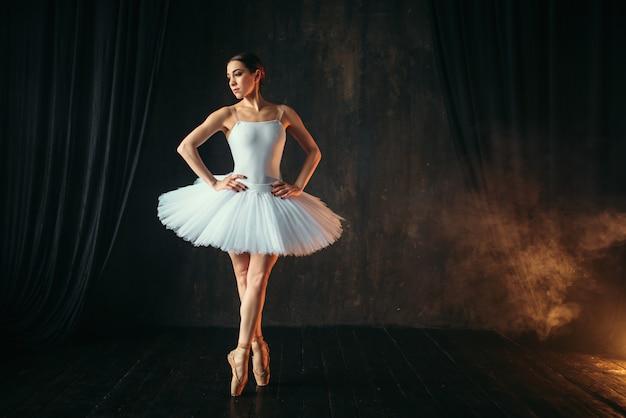 Elegantie ballerina in witte jurk en pointe-schoenen dansen op theatraal podium. klassieke balletdanseropleiding in de klas