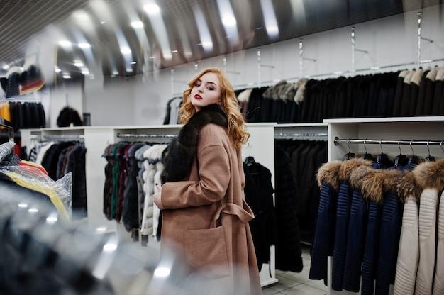 Elegantie blond meisje in bontjas in de winkel van bontjassen en lederen jassen.