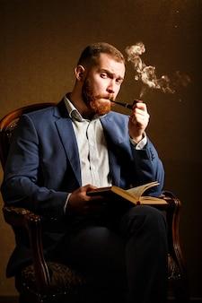 Elegantie en mannelijkheid. portret die van de knappe jonge mens in blauw kostuum een pijp roken en gelezen boek, op stoel zitten.