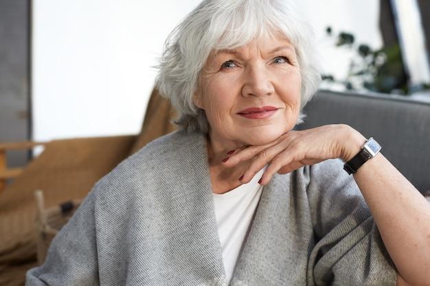 Elegantie, leeftijd, schoonheid en mensenconcept. binnenfoto van charmante elegante senior volwassen vrouw genieten van vrije tijd thuis, zittend op de bank in een stijlvolle woonkamer interieur, gelukkig lachend