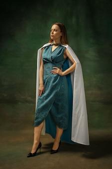 Elegantie poseren. portret van middeleeuwse jonge vrouw in blauwe vintage kleding op donkere achtergrond. vrouwelijk model als hertogin, koninklijk persoon. concept vergelijking van tijdperken, modern, mode, schoonheid.