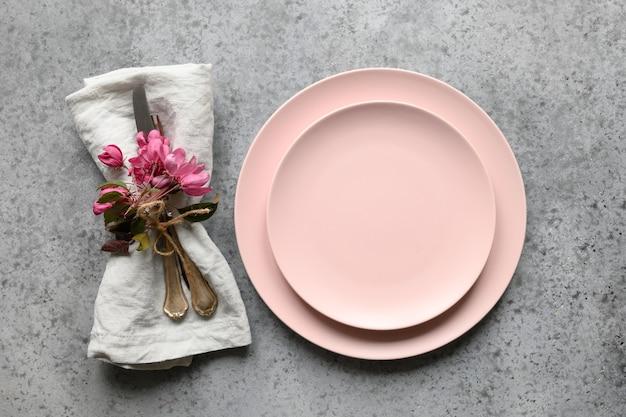 Elegantie romantische tafelsetting met appelboombloemen op grijze steen.