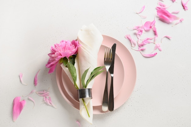 Elegantie romantische tafelsetting met roze pioenroos bloemen op een witte tafel.