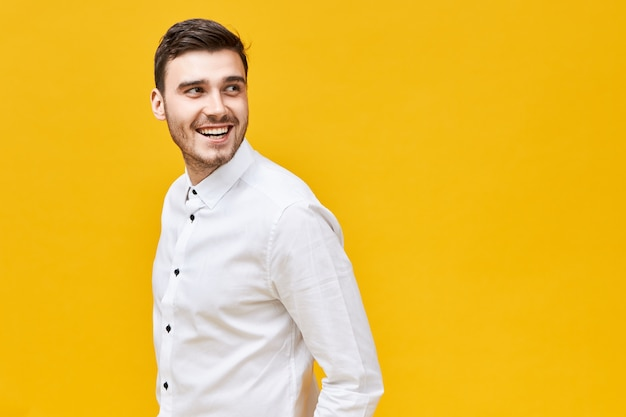 Elegantie, stijl en mannelijkheid concept. aantrekkelijk trendy ogende jonge brunette man met borstelhaar en gelukkige glimlach uiten vertrouwen poseren geïsoleerd op gele muur, hoofd ronddraaien