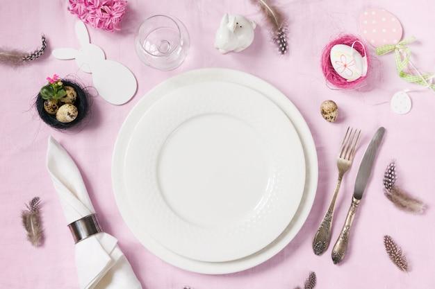 Elegantie tabel voorjaar roze bloemen op roze linnen tafellaken instellen. bovenaanzicht
