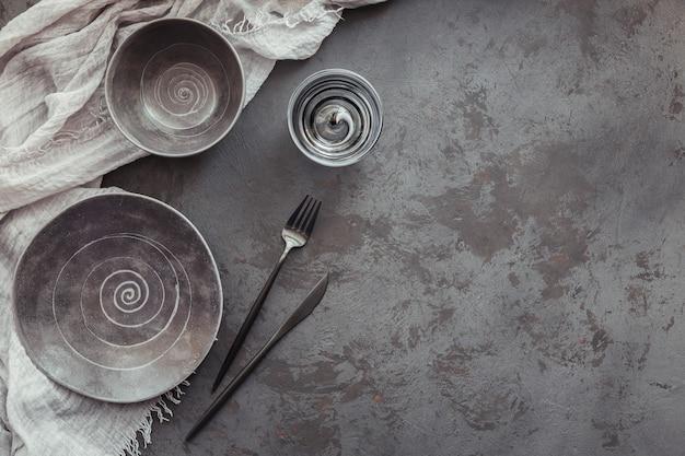 Elegantie tafelsetting met gebreid grijs servet, bestek, keramische borden en glazen op donkere tafel. vakantie moderne tafeldecoratie. romantisch diner.
