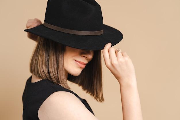 Elegantieportret van een jonge stijlvolle vrouw met een zwarte hoed