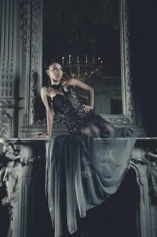 Elegantievrouw met vliegende kleding in paleisruimte