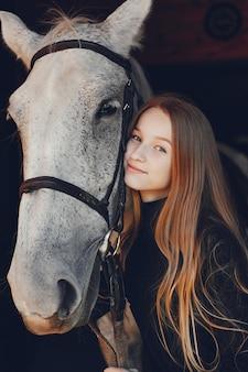 Elegantsmeisje met een paard in een boerderij