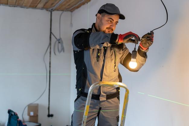 Elektricien aangesloten draden met elkaar en lamp in stopcontact verlicht met een fel licht
