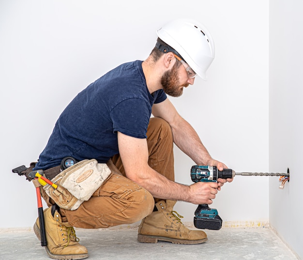 Elektricien bouwer aan het werk, installatie van lampen op hoogte. professioneel in overall met boormachine. op de reparatiesite. het concept van werken als professional.