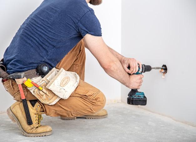 Elektricien bouwer aan het werk, installatie van lampen op hoogte. professioneel in overall met boormachine.